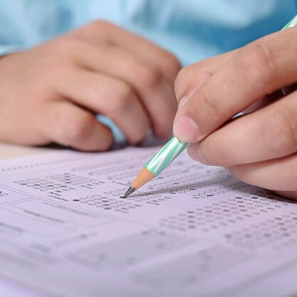 A close up of a person filling out a Scantron sheet.