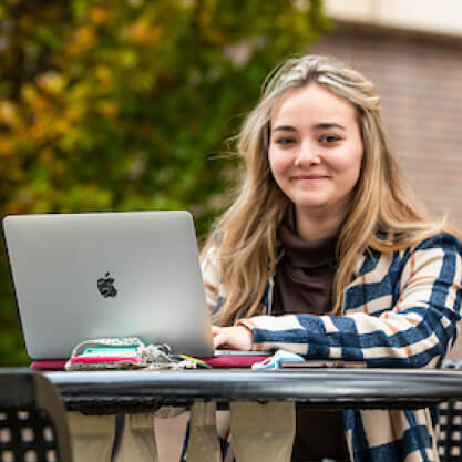 A student smiles outdoors while using their laptop at a bench.