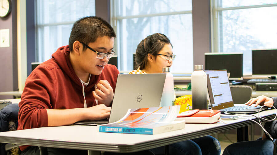 Students working with textbooks and laptops on homeworkin the the tutoring center