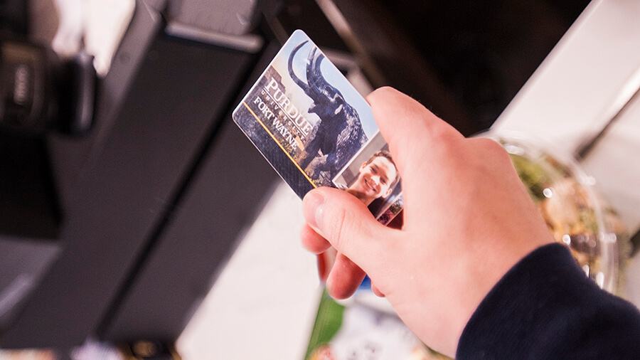 A student hands their Mastodon Card to a cashier.