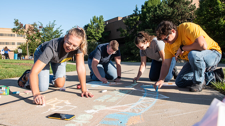 A student organization creates sidewalk chalk artwork during a campus event.