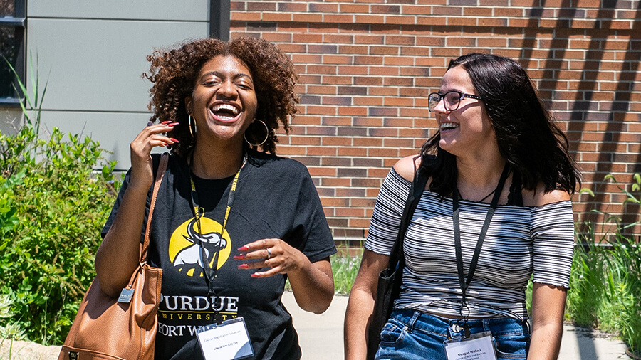 Two students laugh and walk together on campus.