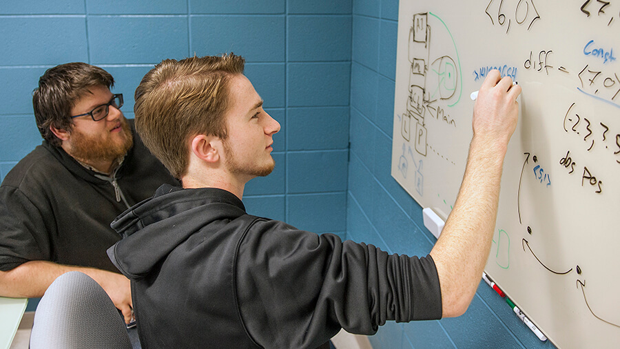 A student writes on an erasable white board while another student watches.