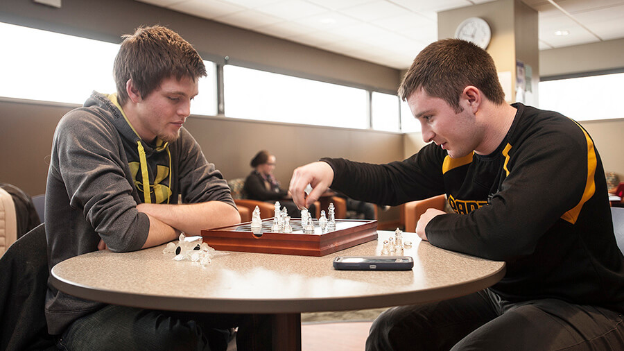 Two students are engaged in a chess match.