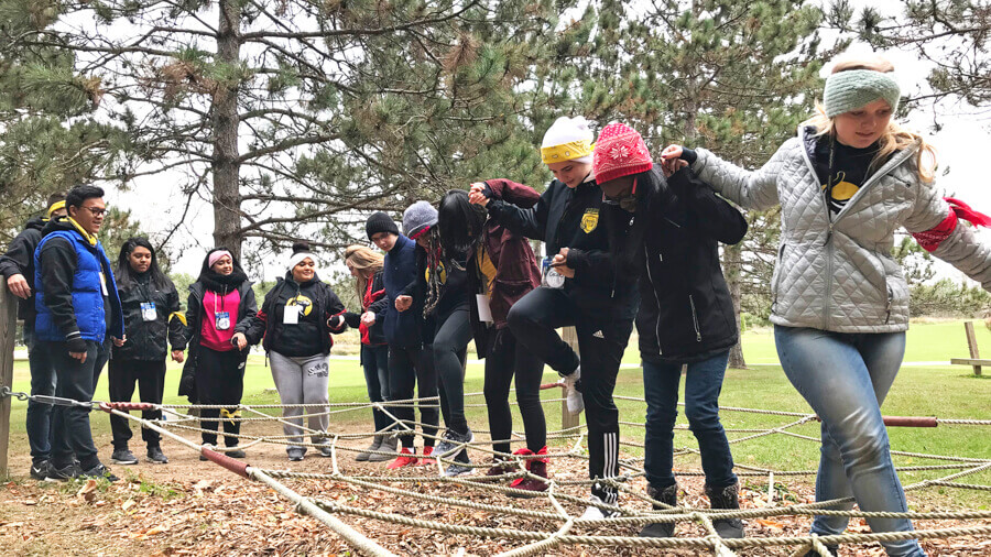 Students working together at the freshman leadership retreating to get through an obstacle course