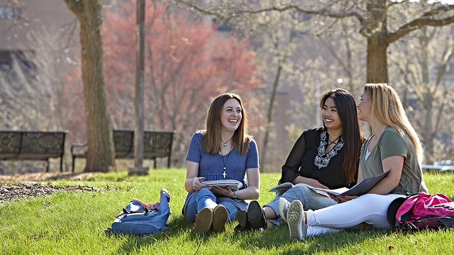 Three students study together outdoors on campus