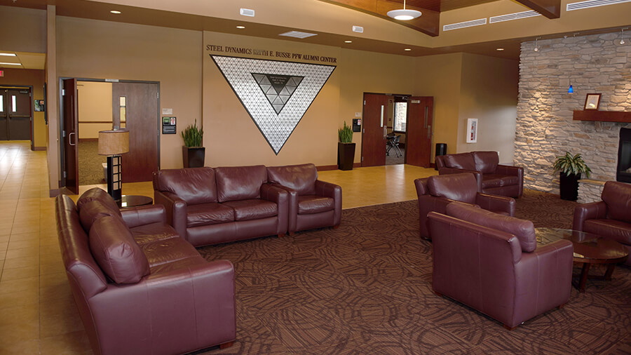 A wide-angle view of the Alumni Center lobby, featuring the alumni triangle display.