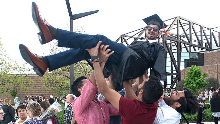 Proud friends lifting their graduate above their heads