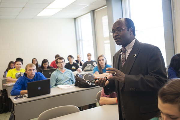 Photo of Professor Joespeter Mbuba, Ph.D., with students.