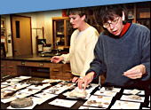 Two individuals looking at artifacts in the archaeology laboratory.
