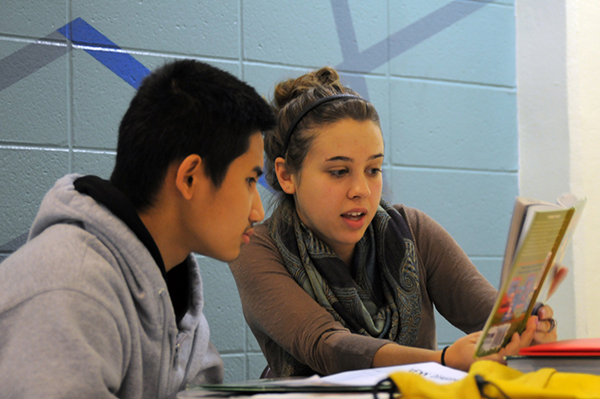 Photo of a secondary education student tutoring an eighth grade student in the IPFW New Immigrant program.