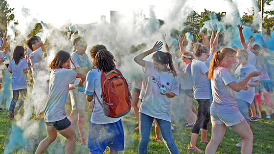 A group of students throw colored powder at one another during a color run event.
