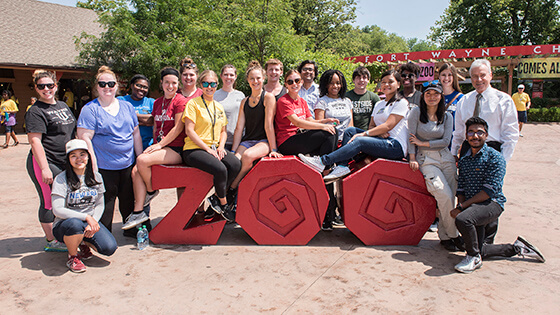 A group of students pose with Chancellor Elsenbaumer at the Fort Wayne Children's Zoo sign.