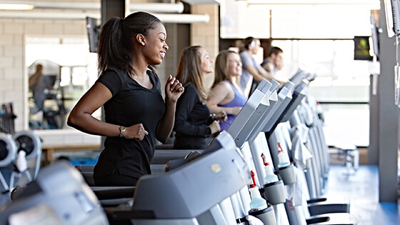 A group of students use treadmills.
