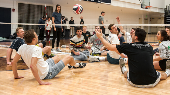 A group of students sitting on the floor play a variant of volleyball.