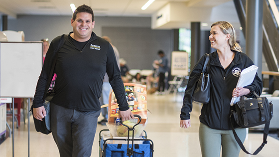 Two faculty members smile while walking down a hallway in Walb Union.