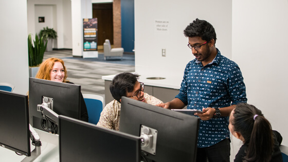 Four students smile while meeting in a campus computer lab.