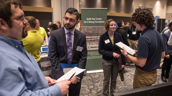 Two students talk to potential employers at a career fair.