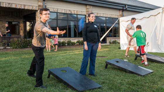 Two alumni take part in a game of cornhole during a Mastodon Roast event.