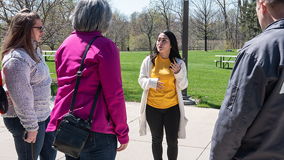 A student guide answers questions during a tour around campus.