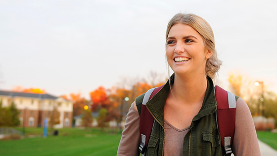 A smiling student enjoys a nice day on campus