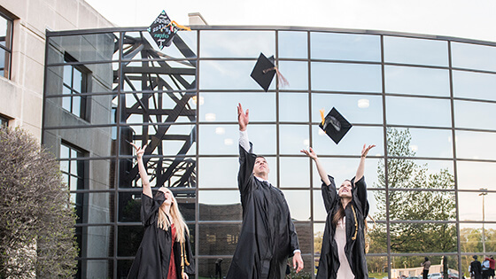 Graduates throwing their caps in the air in front of a glass building