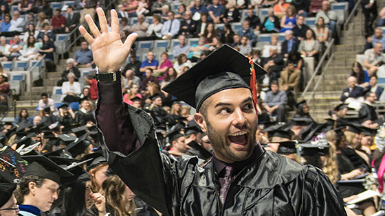 A graduate waving at his family in the crowd