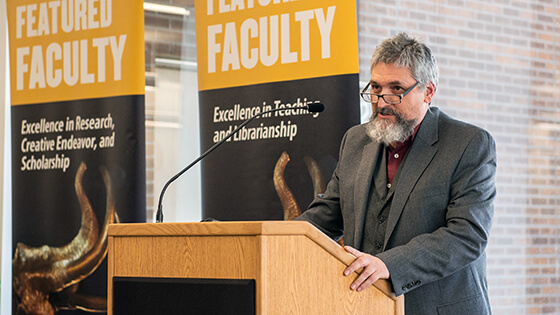 A faculty member speaks at a podium during a Featured Faculty event.