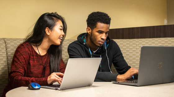 Two students study quietly at a table in a Kettler Hall study lounge.
