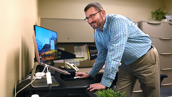 An employee uses a computer at a standing desk.