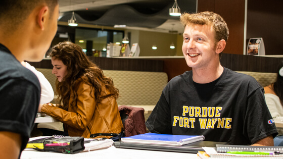 A student smiles while talking to another at the same table.