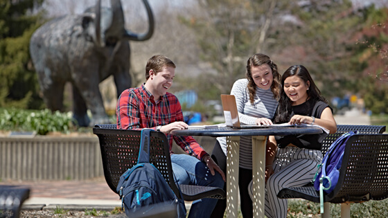 Three students laugh as they study outside at a table.