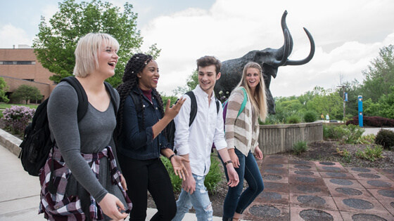Students walking by Mastodon statue