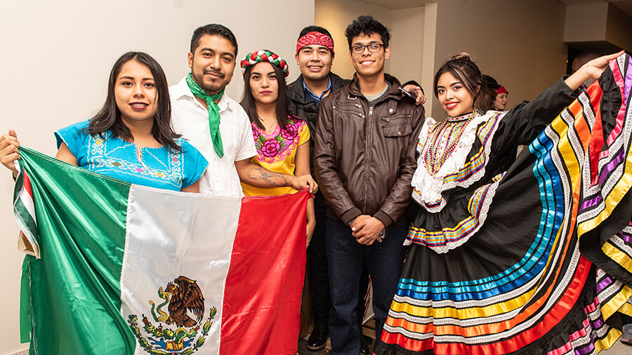 Students posing for a photo holding Mexico's flag