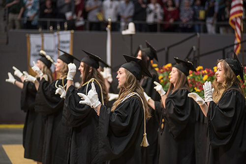 Graduates interpret the National Anthem with American Sign Language at commencement.