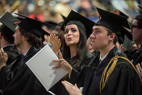 A graduate blows a kiss to their family in the crowd.