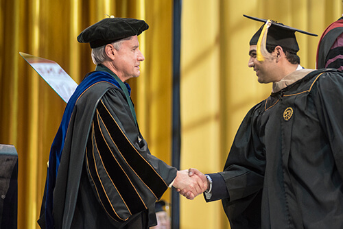 Chancellor Elsenbaumer shakes the hand of a graduate.
