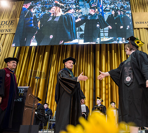A graduate approaches Chancellor Elsenbaumer to shake his hand as they walk during commencement.