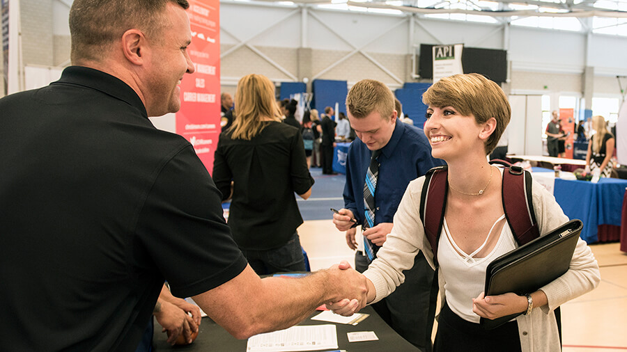 A local employer meets a student at the Purdue Fort Wayne career fair.